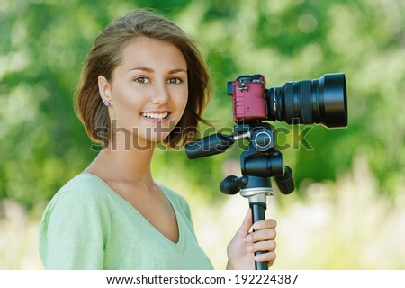 Portrait of smiling beautiful young woman close up with camera, against background of summer green park. - stock photo