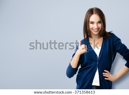 portrait of smiling beautiful young woman in casual smart blue clothing, showing thumbs up gesture, with copyspace for slogan or text message - stock photo