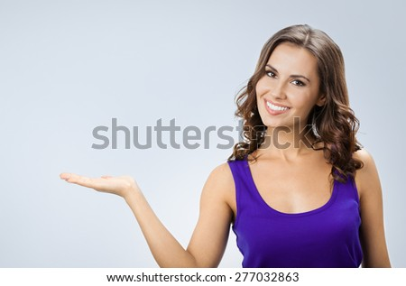 Portrait of smiling beautiful young woman in smart casual violet clothing, showing something or blank copyspace area for slogan or text, on grey background - stock photo