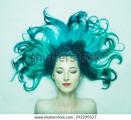 Portrait of smiling beautiful young woman with closed eyes and long hair of turquoise color, top view. Image of mermaid - stock photo