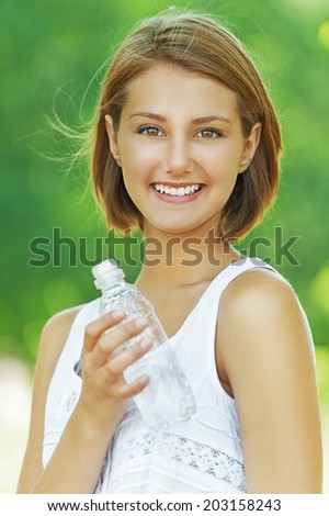 Portrait of smiling beautiful young woman with water bottle, against background of summer green park. - stock photo