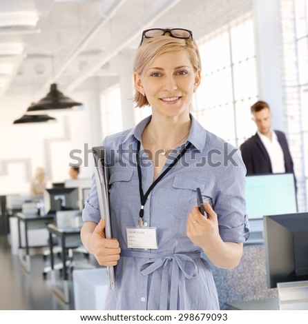 Portrait of smiling blonde businesswoman holding files, looking at camera. - stock photo
