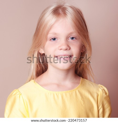 Portrait of smiling blonde girl. Happy young kid posing over beige background. Young model - stock photo