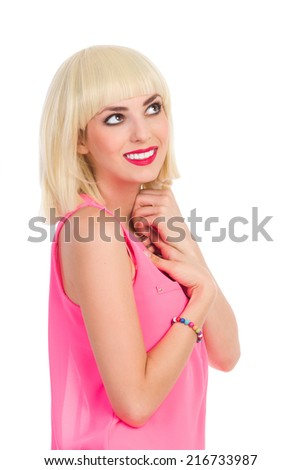 Portrait of smiling blonde woman holding hands on chest and looking up. Waist up studio shot isolated on white. - stock photo