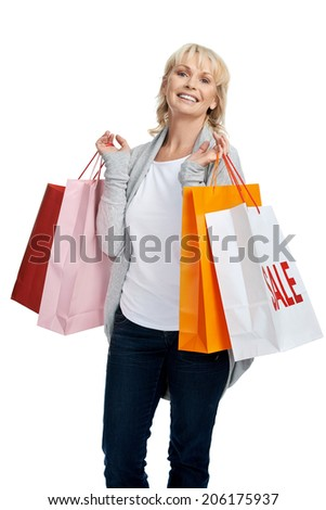 Portrait of smiling blonde woman with shopping bags bought on sale - stock photo