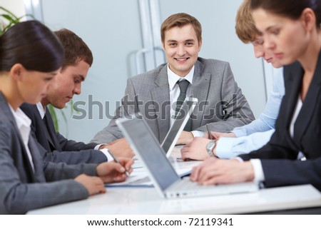 Portrait of smiling boss looking at camera surrounded by employees - stock photo