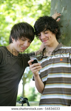 Portrait of smiling boys with a mobile phone - stock photo
