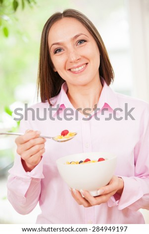 Portrait of smiling brunette woman holding a bowl with corn flakes with berries in her hands - stock photo
