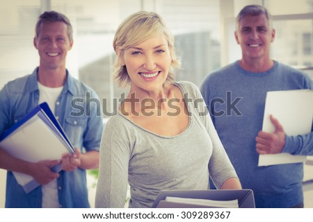 Portrait of smiling business colleagues holding workbooks at office - stock photo