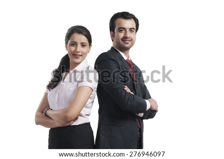 Portrait of smiling business colleagues standing arms crossed over white background - stock photo