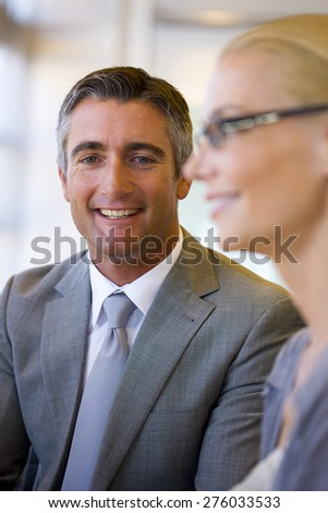 Portrait of smiling business executive with female coworker in the foreground. - stock photo