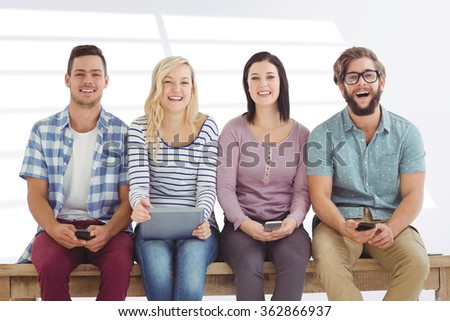 Portrait of smiling business people holding electronic gadgets against grey vignette - stock photo