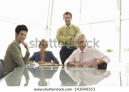 Portrait of smiling business people in conference room - stock photo