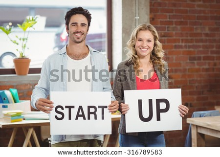 Portrait of smiling business people showing card with start up text while standing in creative office - stock photo