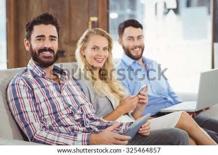 Portrait of smiling business people using technologies in office - stock photo