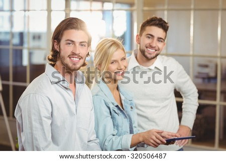 Portrait of smiling business people with laptop standing with male colleagues in creative office - stock photo