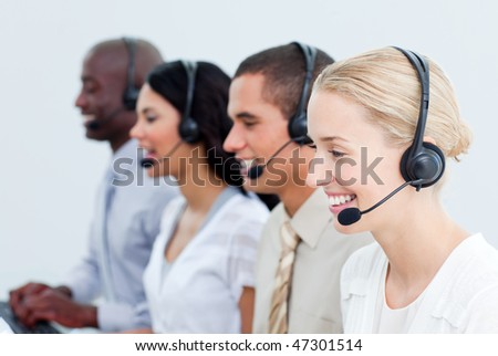 Portrait of smiling business people working in a call center in the office - stock photo