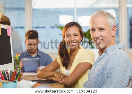 Portrait of smiling business people working in creative office with employees in background - stock photo