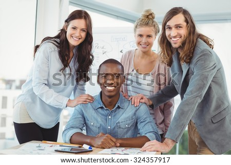 Portrait of smiling business team putting hands on man shoulder at desk in creative office - stock photo