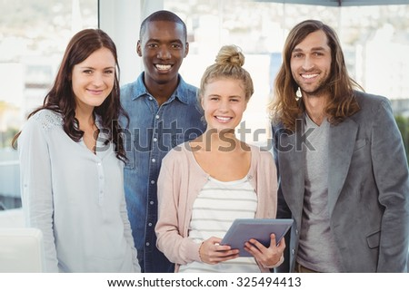Portrait of smiling business team with woman holding digital tablet at office - stock photo