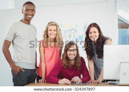 Portrait of smiling business team working at computer desk in office - stock photo