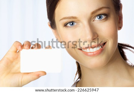 Portrait of smiling business woman giving blank business card, at office - stock photo