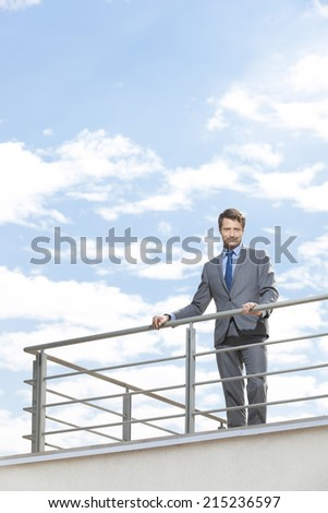 Portrait of smiling businessman at terrace railings against sky - stock photo