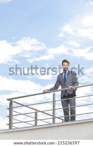 Portrait of smiling businessman at terrace railings against sky - stock photo