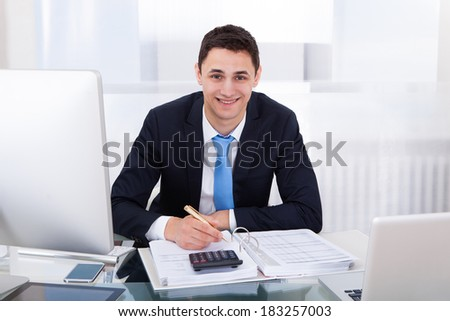 Portrait of smiling businessman calculating tax at desk in office - stock photo