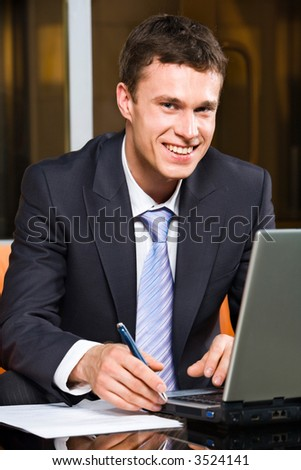 Portrait of smiling businessman holding pen working on the laptop staring at camera - stock photo