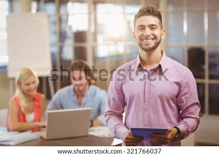 Portrait of smiling businessman using digital tablet in office with colleagues on laptop in background - stock photo