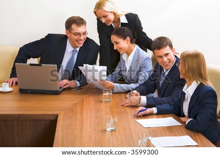 Portrait of smiling businesspeople discussing different questions sitting around the table with an opened laptop, documents and glasses on it - stock photo