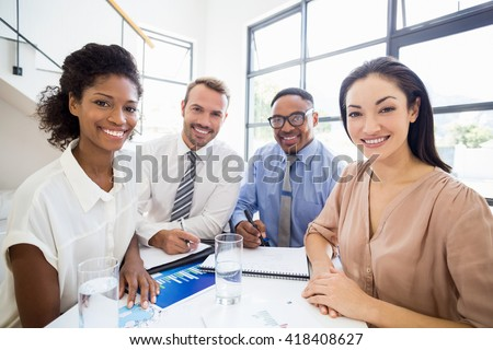 Portrait of smiling businesspeople during a meeting in office - stock photo