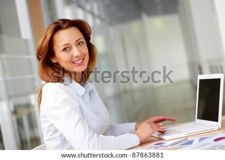Portrait of smiling businesswoman at workplace - stock photo
