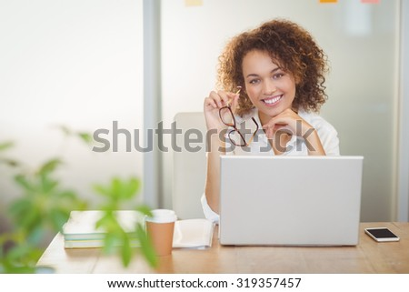 Portrait of smiling businesswoman holding eyeglasses sitting by laptop on desk in office - stock photo
