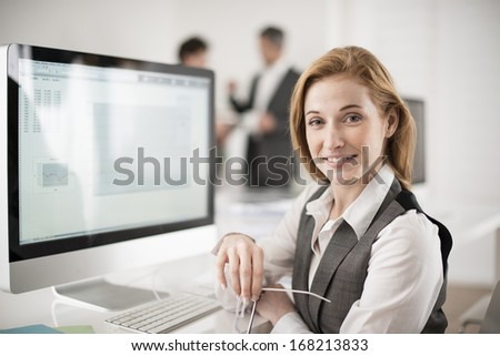 portrait of smiling businesswoman in front of computer - stock photo