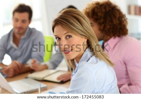 Portrait of smiling businesswoman in meeting - stock photo