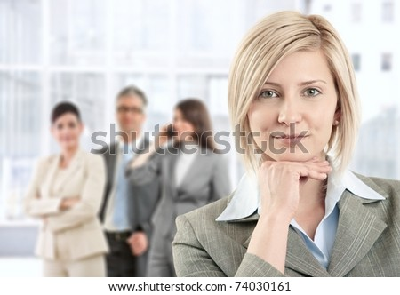 Portrait of smiling businesswoman posing at camera with team in background of office lobby.? - stock photo