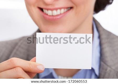 Portrait Of Smiling Businesswoman Showing Visiting Card - stock photo