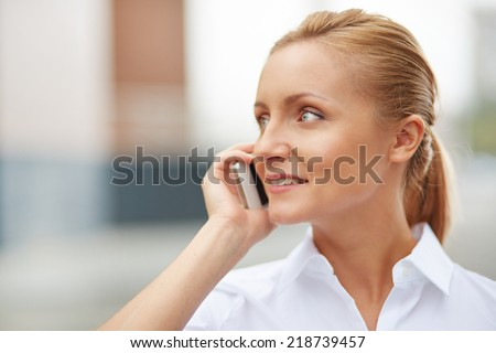Portrait of smiling businesswoman speaking on the cellular phone - stock photo
