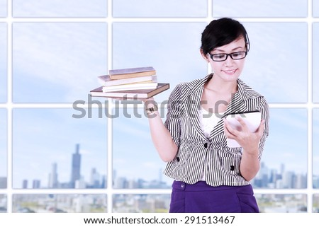 Portrait of smiling businesswoman using tablet pc at modern office - stock photo