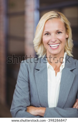 Portrait of smiling businesswoman with arms crossed while standing in office - stock photo