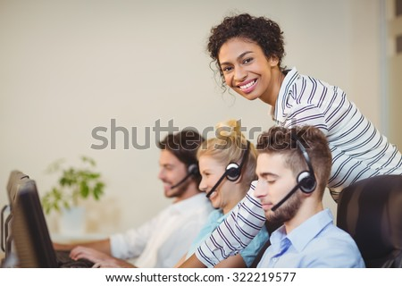 Portrait of smiling businesswoman with employees in call center - stock photo