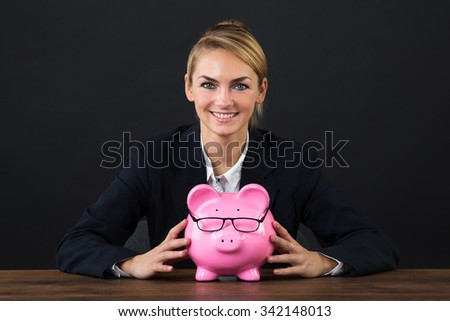 Portrait of smiling businesswoman with piggybank on desk over gray background - stock photo