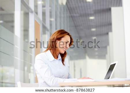 Portrait of smiling businesswoman working with laptop - stock photo