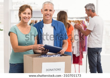 Portrait of smiling casual business colleagues with donation box in the office - stock photo