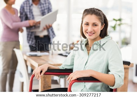 Portrait of smiling casual businesswoman in wheelchair in the office - stock photo