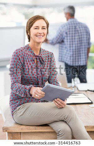 Portrait of smiling casual businesswoman with tablet in the office - stock photo