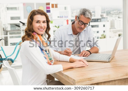 Portrait of smiling casual designer in front of her working colleague in the office - stock photo