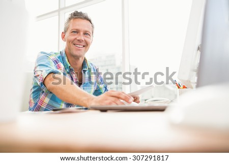 Portrait of smiling casual designer working with computer in the office - stock photo